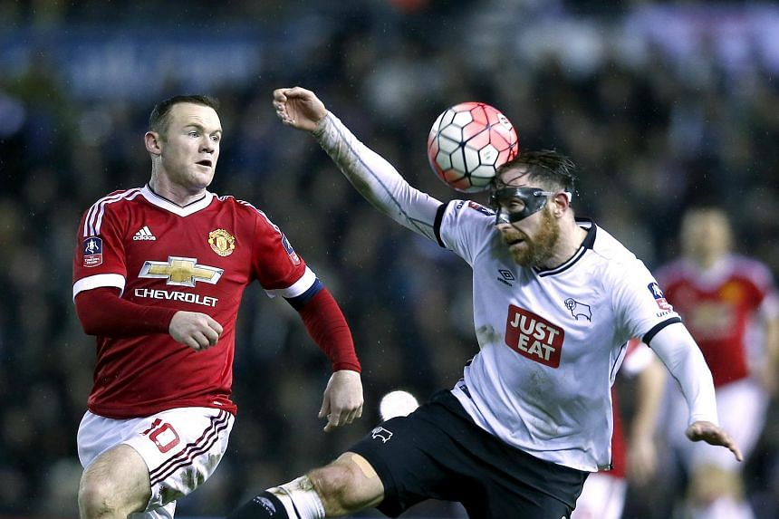 Manchester United's Wayne Rooney (left) in action with Derby's Richard Keogh.
