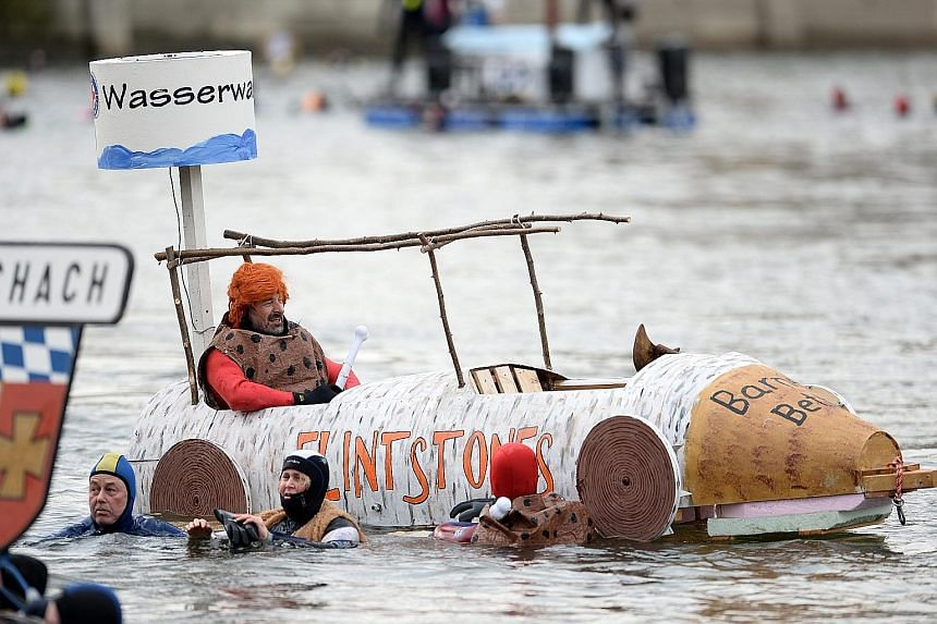 A participant (left) dressed as Fred Flintstone, the lead character in the TV cartoon The Flintstones, sitting in a handmade boat on the Danube river, while other costumed swimmers (above) wave to spectators during the 47th Donauschwimmen (Danube Swi