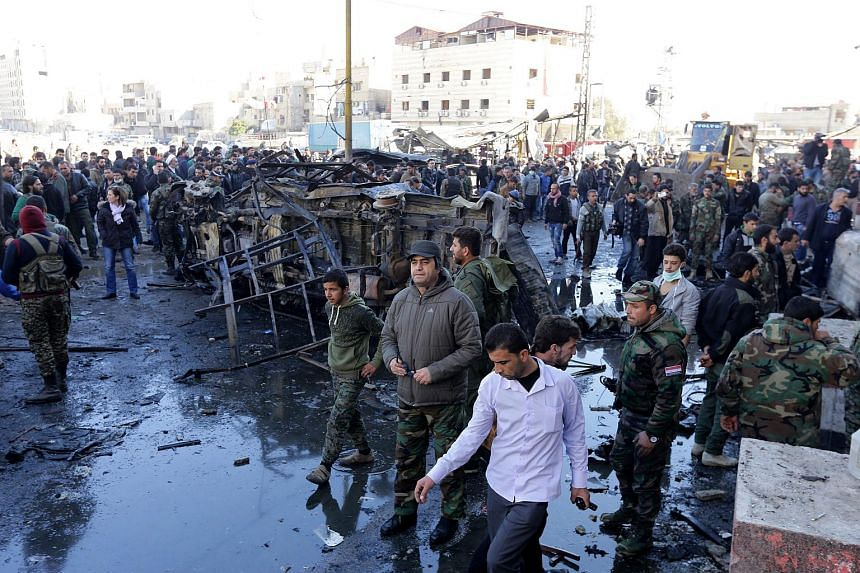 Syrian people and soldiers gather at the site of a bombing in Damascus on Jan 31, 2016.
