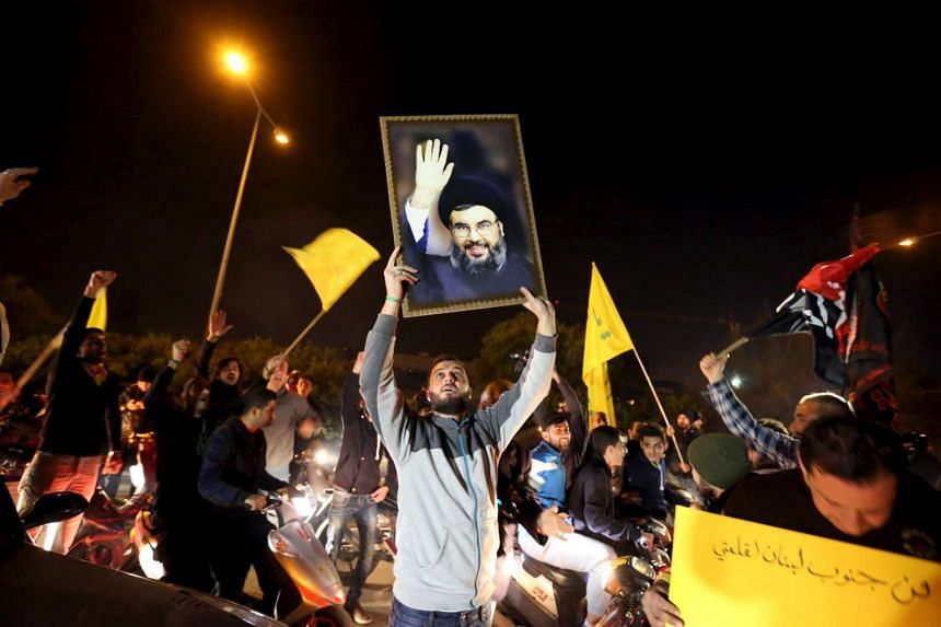 Hezbollah supporters carry a picture of their leader Sayyed Hassan Nasrallah and Hezbollah flag in Lebanon, on Dec 28, 2015.