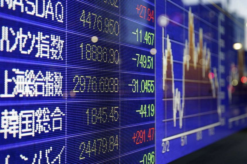 The Shanghai Stock Exchange Composite Index is displayed on an electronic stock board outside a securities firm in Tokyo.