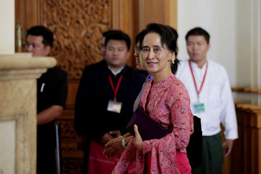 Myanmar democracy leader Aung San Suu Kyi (front) leaves after attending the first day of a new parliament session in Naypyitaw, Myanmar, on Feb 1, 2016.