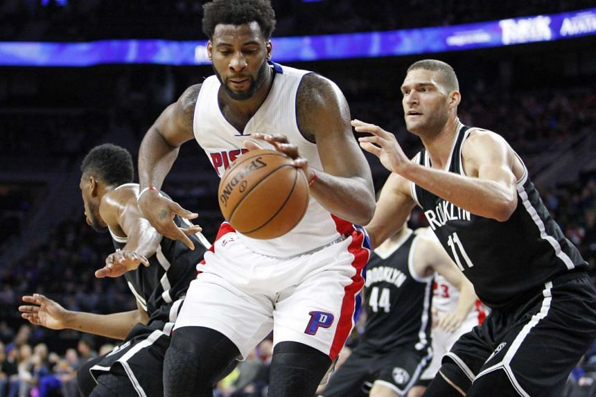 Detroit Pistons center Andre Drummond (in white) dribbles the ball as Brooklyn Nets center Brook Lopez defends.