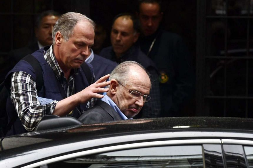A policeman (left) puts former IMF head Rodrigo Rato (centre) into a vehicle outside his home in Madrid.