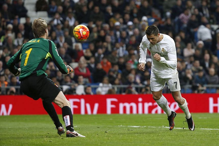 Real Madrid forward Cristiano Ronaldo heads past Giedrius Arlauskis to secure his hat-trick during Real's 6-0 rout of Espanyol yesterday.