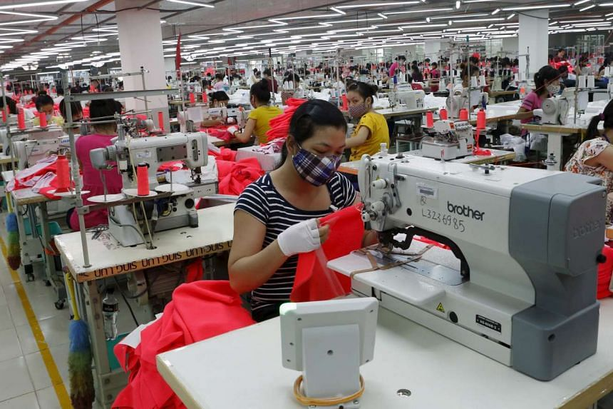 Labourers working at a garment factory outside Hanoi on Aug 19, 2014.