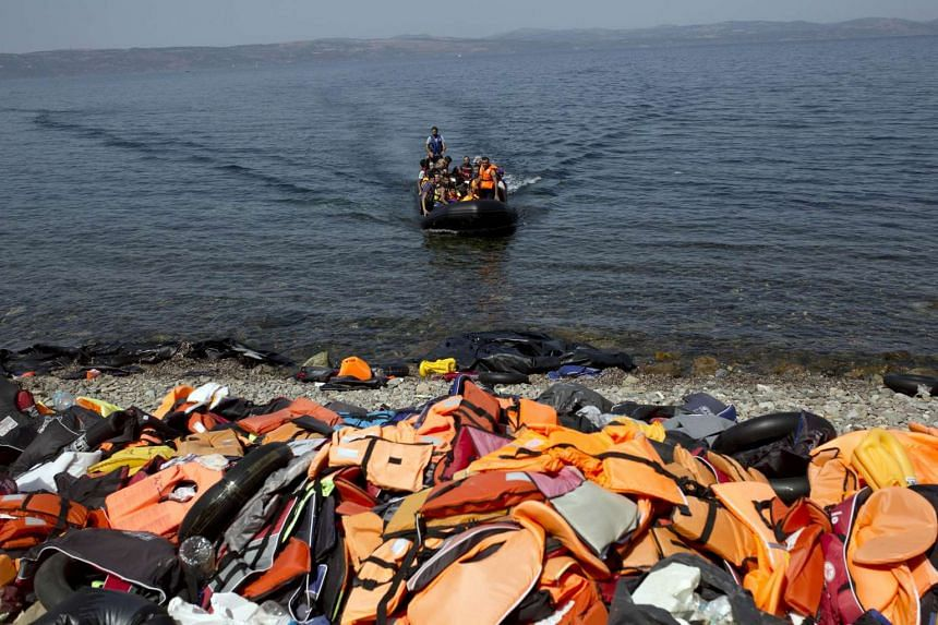 Migrants arrive on the shores of the Greek island of Lesbos after crossing the Aegean Sea from Turkey on a dinghy on Sept 10, 2015.
