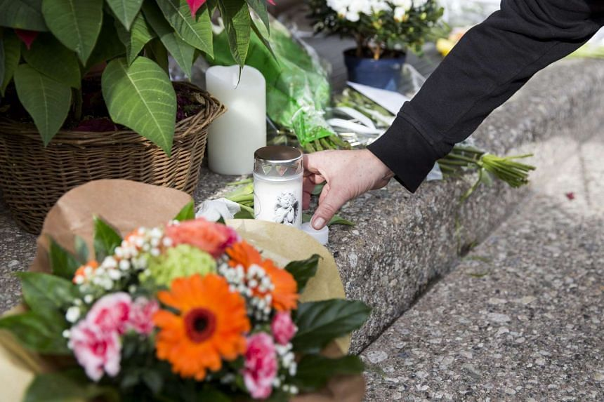 People lay flowers in front of the entrance of the restaurant 'Hotel de Ville' of late Swiss chef Benoit Violier in Crissier, western Switzerland, on Feb 1, 2016.