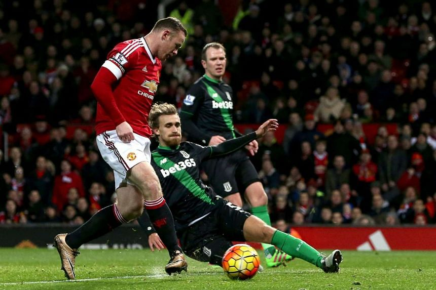Manchester United's Wayne Rooney (left) shoots to score during the English Premier League soccer match between Manchester United and Stoke City at the Old Trafford Stadium , Manchester, Britain, on Feb 2, 2016.