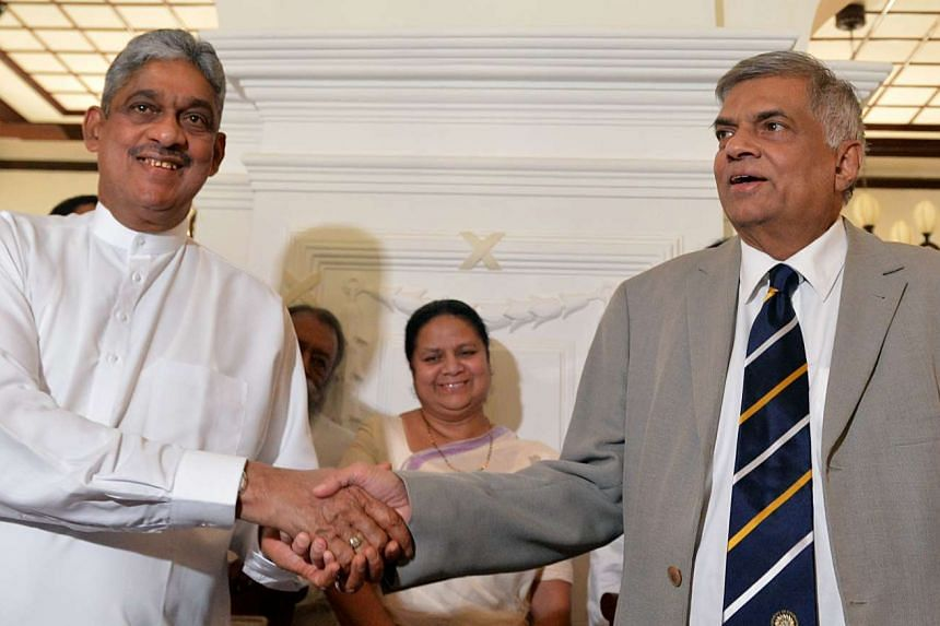 Sarath Fonseka (left) and Ranil Wickremesinghe (right) shake hands during an agreement signing ceremony in Colombo on Feb 3, 2016.