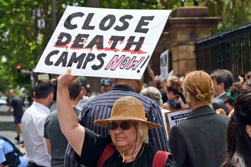 A pro-refugee protester holds up a placard outside the Transfield Services annual general meeting in Sydney on Oct 28, 2015. Transfield runs Australia's offshore detention centres on the Pacific island of Nauru and Papua New Guinea's Manus Island.