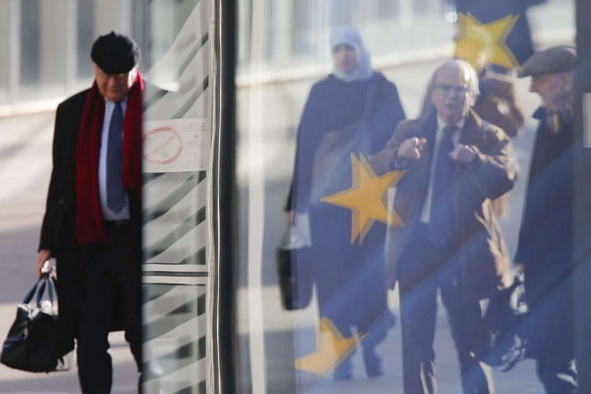 People and the European flag are reflected on a window of the EU commission headquarters in Brussels.