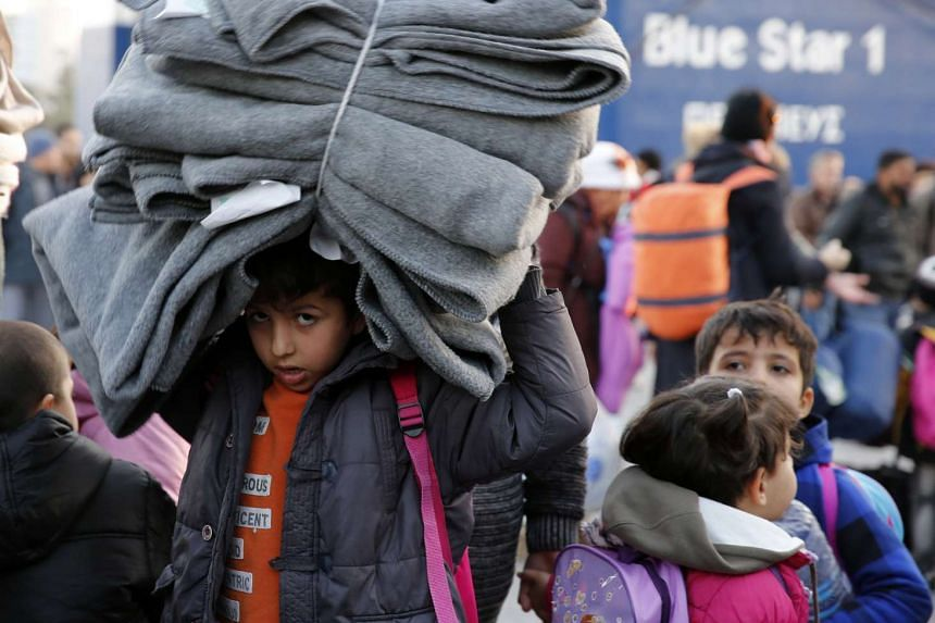 A migrant child carries blankets as refugees and migrants disembark from a passenger ferry at the port of Piraeus, near Athens, Greece.