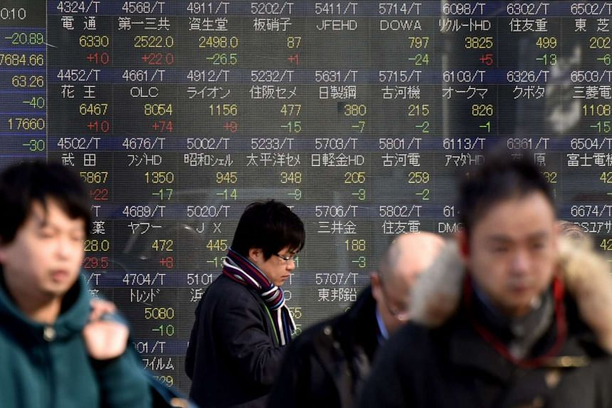 Pedestrians walk past a stock prices board showing figures from the Tokyo Stock Exchange on Feb 2, 2016.