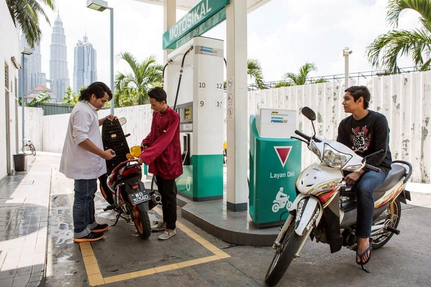 A customer refuelling his motorcycle at a Petronas station in Kuala Lumpur.