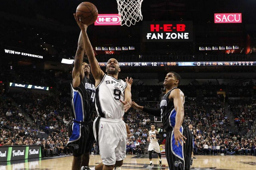 San Antonio Spurs point guard Tony Parker (centre) shoots the ball past Orlando Magic players.