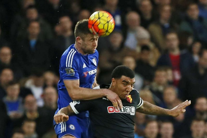 Chelsea's Gary Cahill in action with Watford's Troy Deeney.