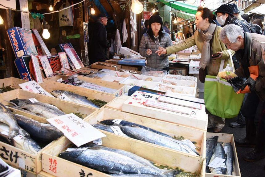 Shoppers select salmon at a market in Tokyo on Dec 25, 2015.