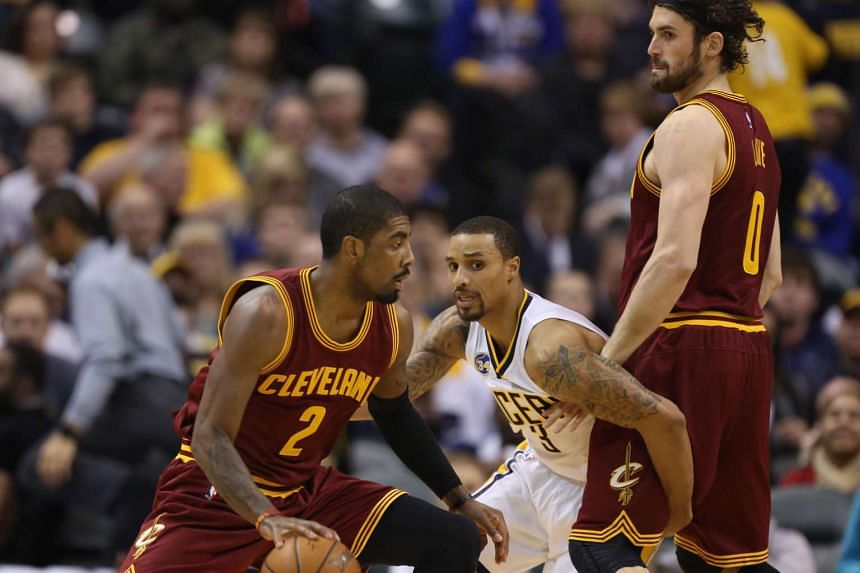 Cleveland guard Kyrie Irving (left) dribbling the ball as Indiana guard George Hill (centre) tries to defend against him. The Cavaliers won 111-106 in overtime.