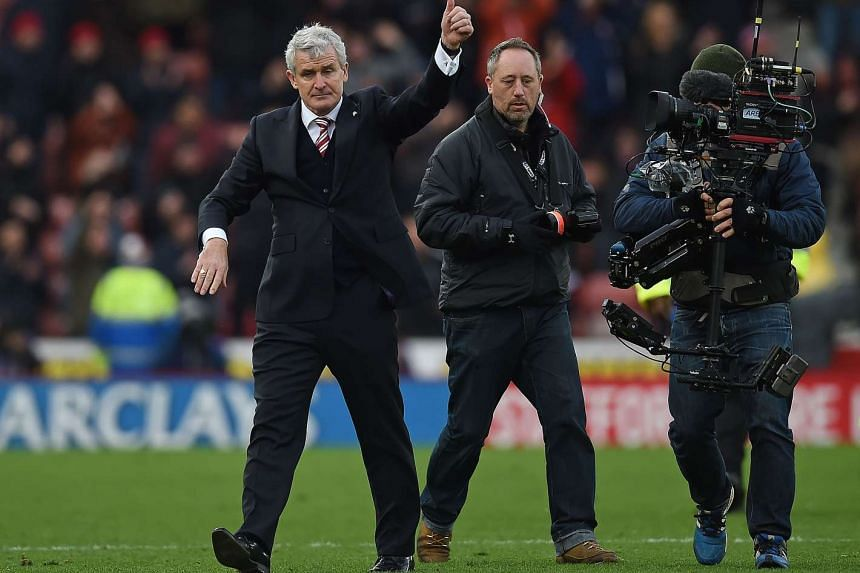 A television camera operator films Stoke City's manager Mark Hughes during the English Premier League football match between Stoke City and Manchester City.