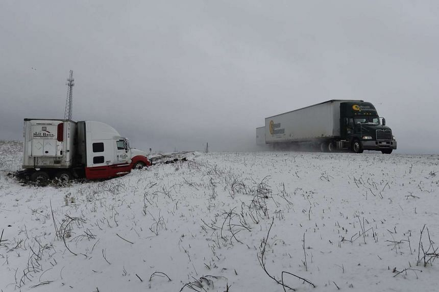 A semi truck passes another semi truck in the ditch along Interstate 35 outside of Des Moines, Iowa.
