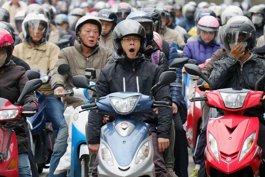 A commuter yawns while waiting for a green traffic light in Taipei on Nov 26, 2015.