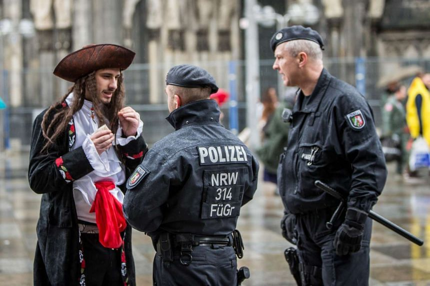 Members of the German police talk to a man dressed as a pirate in Cologne, Germany, on Feb 4, 2016.