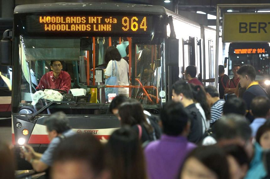 Early morning commuters at Woodlands bus interchange boarding buses.