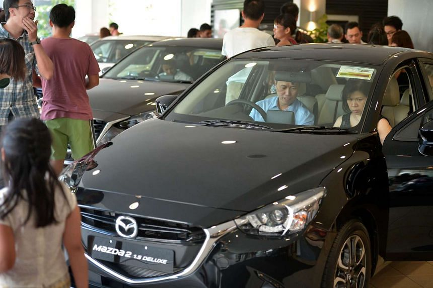 People checking out cars in the Mazda showroom.