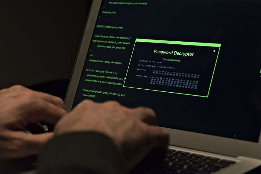 Posed photo of a man attempting to hack into a computer.