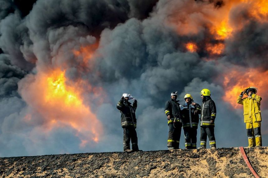 Firefighters try to put out the fire in an oil tank in the port of Es Sider in Libya in January 2016 after ISIS attacks.