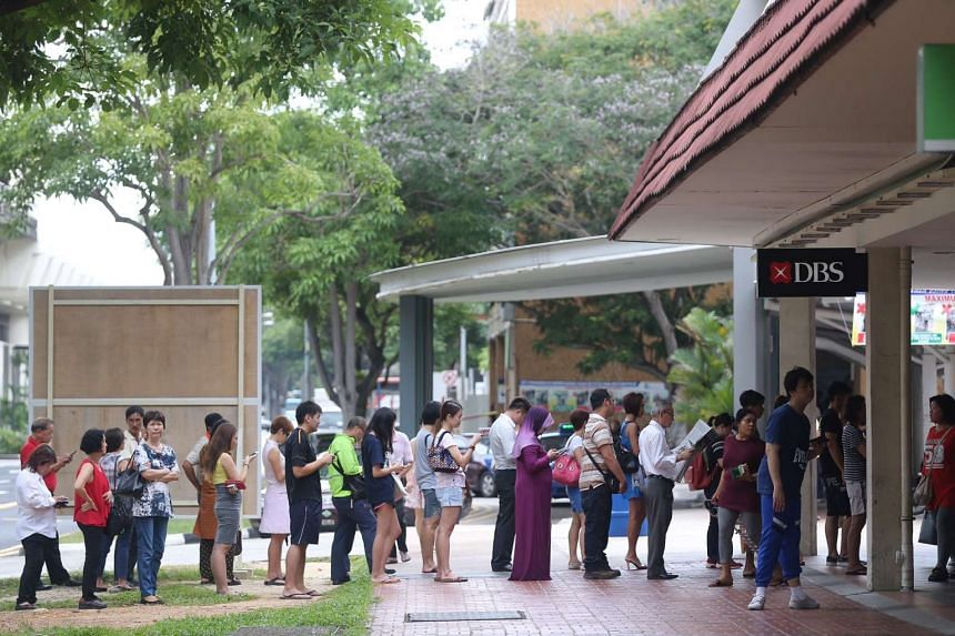 Members of the public queue to deposit cash at DBS Bank in Bedok Town Centre.