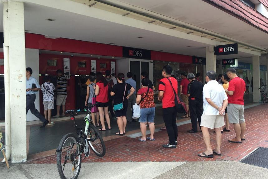 People line up to deposit cash at a DBS Bank branch in Bedok Central.