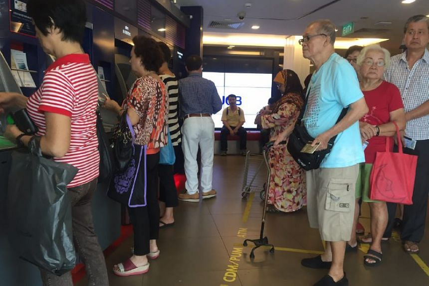 Mr Michael Lim (in light blue), 78, queues up at UOB Bank to do a cash deposit for Li Chun.
