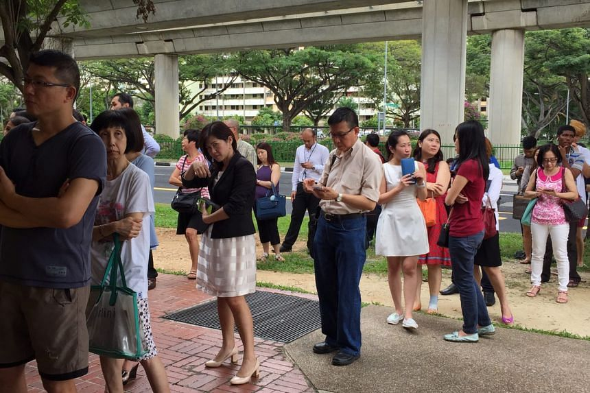 Ms Charlyn Tan (in a white dress) and Ms Wong Yen Nee (in red T-shirt and jeans) queue up to deposit their cash for Li Chun.