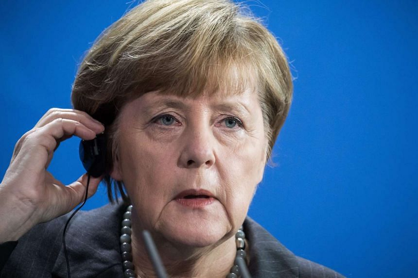 German Chancellor Angela Merkel gets an earpiece in place for a press conference.