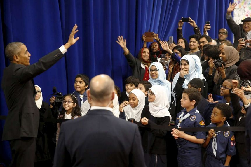 Mr Obama waves farewell to students after his remarks at the mosque in Maryland.
