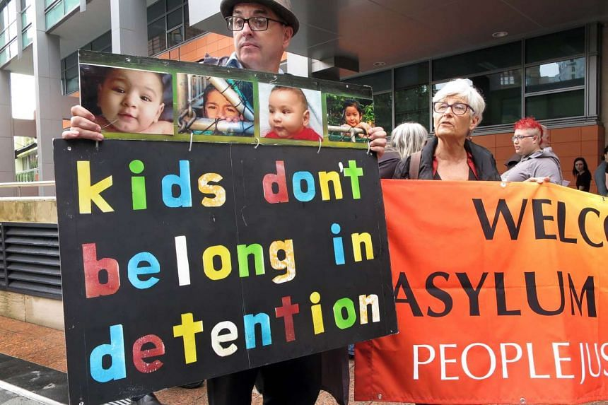 People hold placards at a protest outside an immigration office in Sydney on Feb 4, 2016, as Australian church leaders said they would offer sanctuary to asylum-seeker adults and children set to be deported.