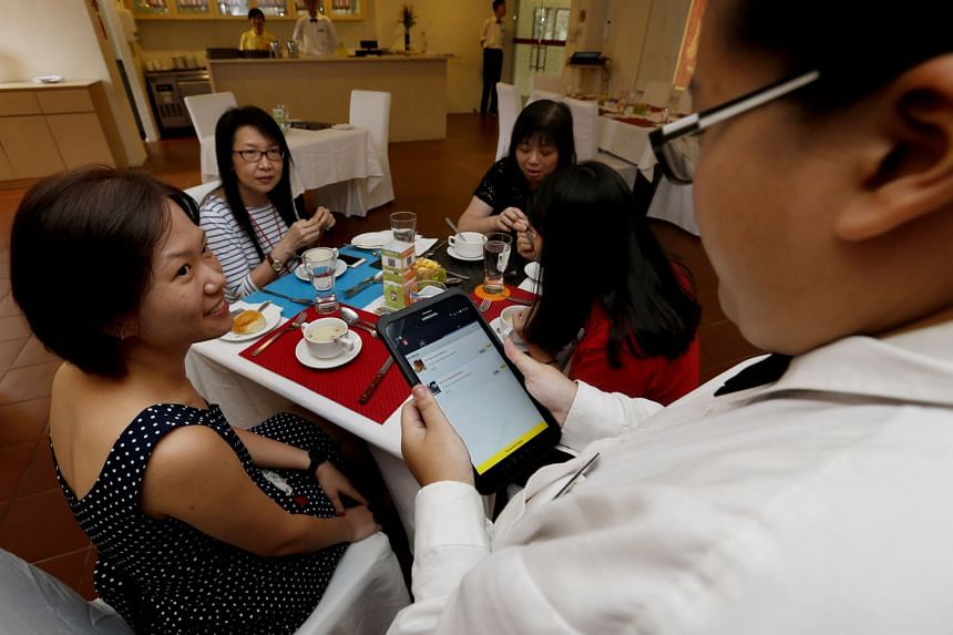 Account executive Ms Chua having her order taken by a waiter using the colour-coded system. Each customer's place at a table is marked by a mat or coaster of a different colour. Waiters then take orders using a tablet that locks in the customer's order ba