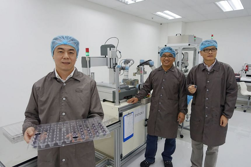 Mr Chee (left), Moveon Technologies' chief executive, with engineers Randy Hipona (centre) and Xie Jie Lin, who have been seconded from A*Star to help boost the company's R&D processes since 2014. The optical solutions firm spends almost $2 million a year