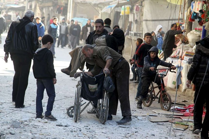Men help a woman out of a site damaged by what activists said was an airstrike by forces loyal to Syria's president Bashar Al-Assad.