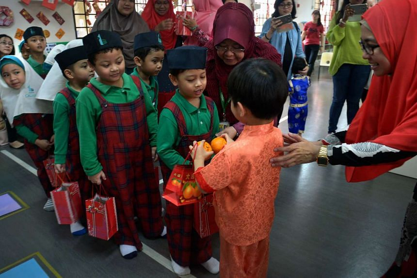 Ahmad Nabil a student from An-Nahdhah Mosque receives mandarin oranges from Jaylen Loo, a student from My First Skool Childcare.