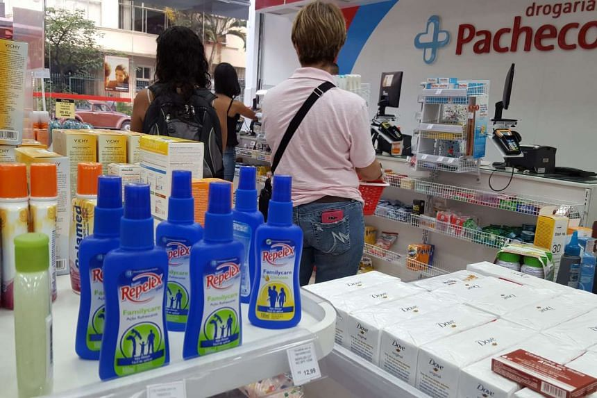 Bottles of mosquito repellents are stocked on shelves in a pharmacy in Brazil on Feb 5, 2016.