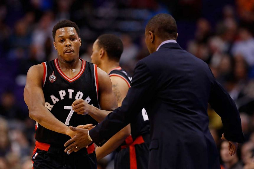 Kyle Lowry of the Toronto Raptors high fives head coach Dwane Casey during the first half of the game against the Phoenix Suns.