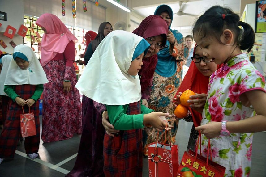 Maika Lemonil, a student from An-Nahdhah Mosque receives mandarin oranges from Tao Lin Yu, a student from My First Skool Childcare.