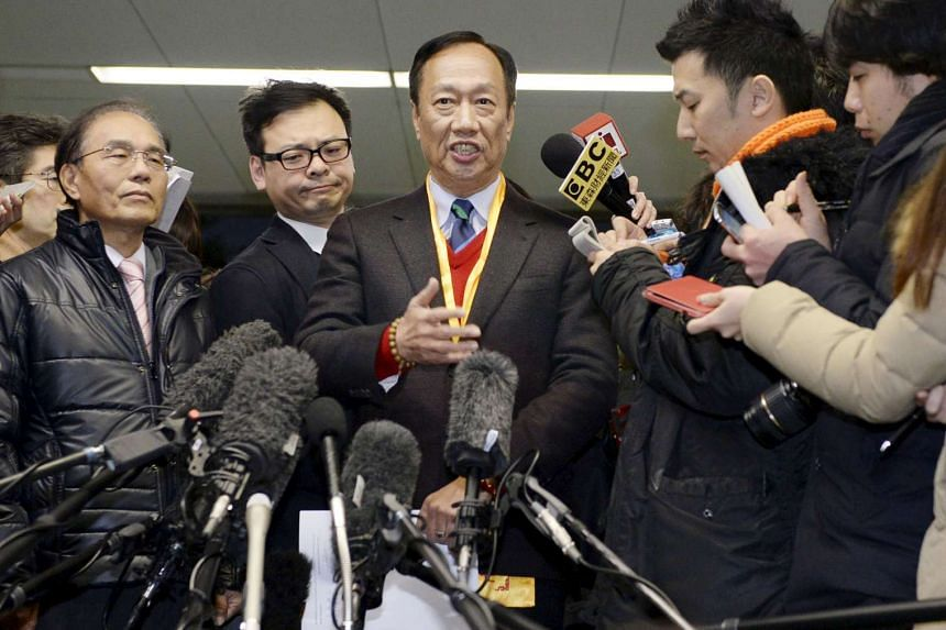 Terry Gou (centre), CEO of Taiwan's Foxconn Technology, speaks to reporters at Sharp's headquarters on Feb 5, 2016.