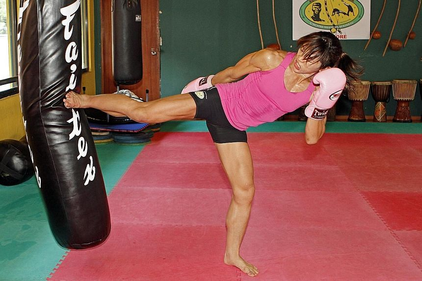 May Ooi practising her kicks at the Brazilian Cultural Centre. The 15 years that she spent swimming competitively has not been for nothing, as it has enabled the 39-year-old to keep fit, giving her more time to hone other aspects of her fight game.