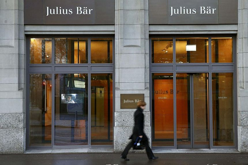 A woman walking past a Julius Baer branch in Zurich, Switzerland, on Feb 1.