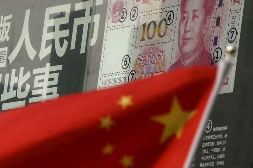 A Chinese flag in front of a poster of a new 100 yuan note at a bank in Beijing on Jan 21.