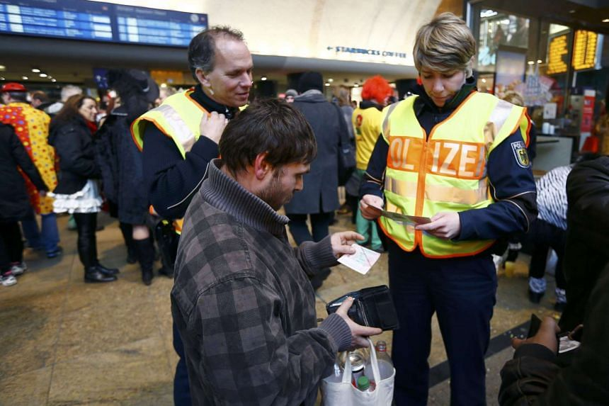 Police check the documents of a man from Kosovo (centre) during the carnival in Cologne.